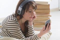 Mujer que escucha un audiolibro imagenes de archivo