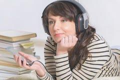 Mujer que escucha un audiolibro foto de archivo libre de regalías