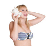 Mujer que escucha un seashell Fotos de archivo