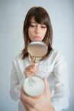 Mujer que escudriña la escritura de la etiqueta de la nutrición Imagen de archivo libre de regalías