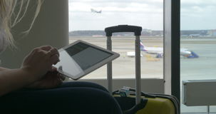 Mujer que espera el vuelo con la tableta almacen de metraje de vídeo