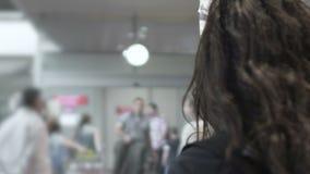 Mujer que espera en las puertas de la llegada del aeropuerto, ayudante personal del hombre de negocios extranjero almacen de video