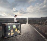 Mujer que espera en un banco con una maleta Imagenes de archivo