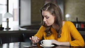 Mujer que espera nervioso en café, comprobando smartphone y saliendo, mala fecha almacen de metraje de vídeo