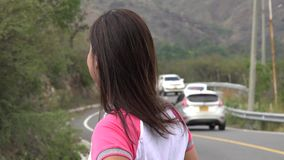 Mujer que espera por el tráfico por carretera almacen de video