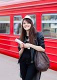Mujer que espera un tren con el boleto en sus manos Imagenes de archivo