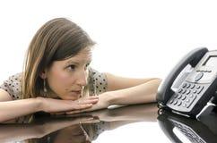 Mujer que espera una llamada de teléfono mientras que mira el teléfono Fotos de archivo