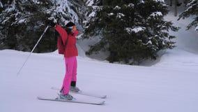 Mujer que esquía abajo de la cuesta del esquí en la montaña entre la mano del bosque del pino al lado almacen de metraje de vídeo