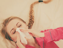 Mujer que está enferma teniendo gripe que miente en cama Imagen de archivo libre de regalías