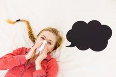 Mujer que está enferma teniendo gripe que miente en cama Imagenes de archivo