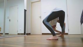 Mujer que estira cerca del espejo en su apartamento El concepto de una forma de vida sana, no un deporte profesional foto de archivo libre de regalías