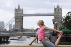 Mujer que estira contra el puente de la torre en Inglaterra Fotografía de archivo
