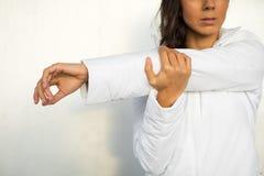 Mujer que estira el brazo y el hombro Imagen de archivo libre de regalías