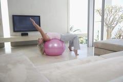Mujer que estira en bola de la aptitud Fotos de archivo libres de regalías