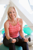 Mujer que estira en bola suiza en la gimnasia Imagen de archivo