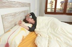 Mujer que estira en cama después de despertar imagenes de archivo