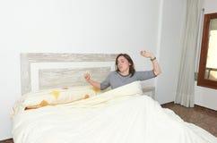Mujer que estira en cama después de despertar foto de archivo