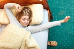 Mujer que estira en cama por mañana después de dormir fotos de archivo