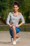 Mujer que estira en el parque Imagen de archivo libre de regalías