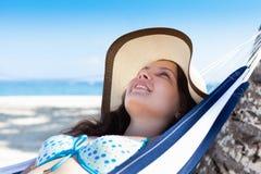 Mujer que estira en hamaca en la playa Imagen de archivo