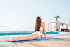 Mujer que estira en la estera de la yoga Imagen de archivo