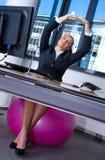 Mujer que estira en oficina Imagenes de archivo