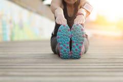 Mujer que estira las piernas antes de ejercicio Maratón Fotos de archivo libres de regalías