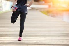 Mujer que estira las piernas antes de ejercicio Maratón Fotografía de archivo