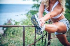 Mujer que estira los músculos antes de actividad del deporte Fotos de archivo libres de regalías