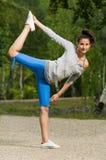 Mujer que estira su pierna en el parque Fotografía de archivo