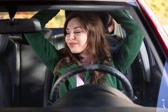 Mujer que estira sus brazos en coche imagenes de archivo