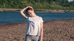 Mujer que estira yoga en la playa por el río en la ciudad Inclinación de la cabeza y de los brazos el estirar Visión hermosa almacen de video