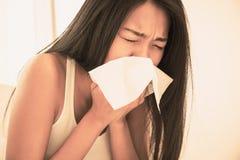 Mujer que estornuda en su cama Foto de archivo