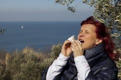 Mujer que estornuda, nariz que sopla en tejido sobre costa de mar imagenes de archivo