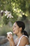 Mujer que estornuda por las flores Foto de archivo