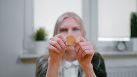Mujer que estudia el bitcoin en manos Opinión del primer de manos de la hembra rubia joven en la ropa elegante que se sienta en l almacen de video