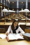 Mujer que estudia en biblioteca fotografía de archivo
