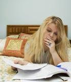 Mujer que estudia en cama Imagenes de archivo