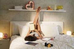 Mujer que estudia en la cama que hace la preparación en la puesta del sol Imagen de archivo