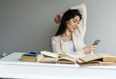 Mujer que estudia para los exámenes con el teléfono en la mano Fotos de archivo libres de regalías