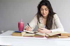 Mujer que estudia para los exámenes con el teléfono en la mano Imagen de archivo