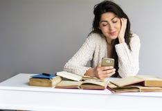 Mujer que estudia para los exámenes con el teléfono en la mano Imagenes de archivo