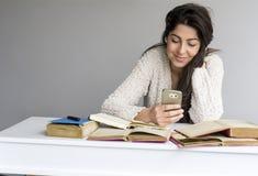 Mujer que estudia para los exámenes con el teléfono en la mano Fotografía de archivo libre de regalías