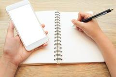 Mujer que estudia y que aprende notas con un smartphone móvil en a Imagen de archivo