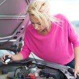 Mujer que examina el motor de coche roto Fotos de archivo