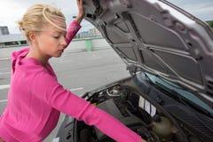 Mujer que examina el motor de coche roto Foto de archivo libre de regalías