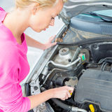 Mujer que examina el motor de coche roto Fotografía de archivo libre de regalías