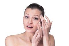Mujer que examina su cara y arrugas que pueden aparecer, aisladas Fotografía de archivo