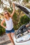 Mujer que examina su motor de coche después de una avería imágenes de archivo libres de regalías