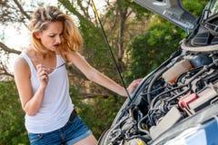 Mujer que examina su motor de coche después de una avería fotos de archivo